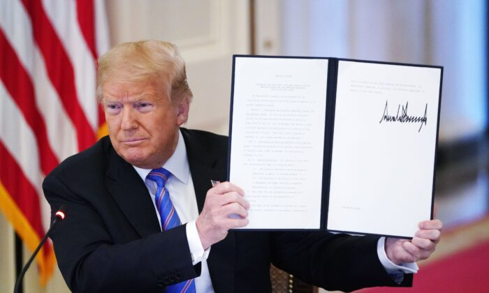 """Former President Donald Trump holds an executive order he signed at the White House in Washington on June 26, 2020 to establish a 20-person Advisory 1776 Commission under the Department of Education to promote """"patriotic education."""" The commission was terminated by President Joe Biden on Jan. 20, 2021. (Mandel Ngan/AFP via Getty Images)"""